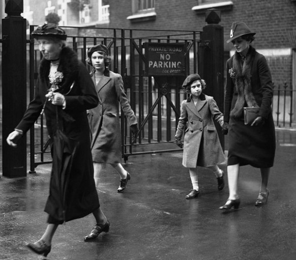 La principessa Elisabetta e la principessa Margaret dopo il loro primo viaggio nella metropolitana. Viaggiarono con una governante e una dama di compagnia da St. James'€™s Park a Tottenham Court Road, in una carrozza ordinaria e insieme agli altri passeggeri. Qui stanno camminando da Tottenham Court Road Station alla sede dell'YMCA. 15 maggio 1939.